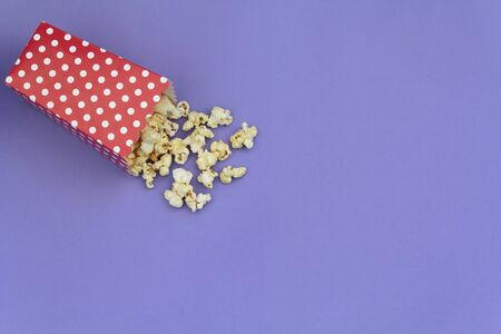 Red box with popcorns on purple background with copy space Stock Photo