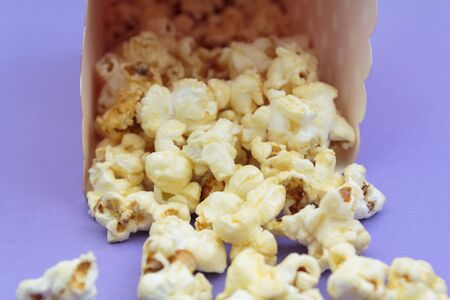 Popcorn falling out of the box on purple background