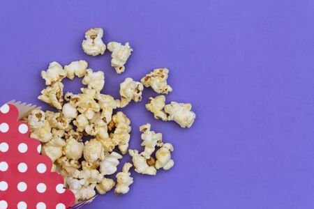 Popcorn box with polka dots on purple background with copy space