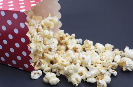 Popcorn falling out of the box on black background