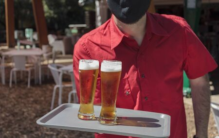 Waiter with protective mask on face holding tray with beers