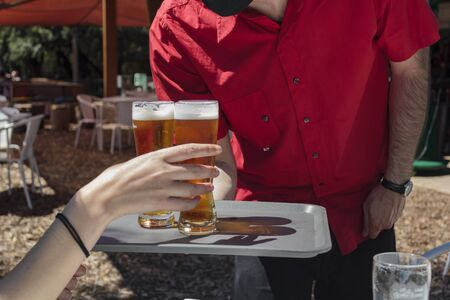 Waiter with protective mask on face serving beer to client at outdoor bar Reklamní fotografie