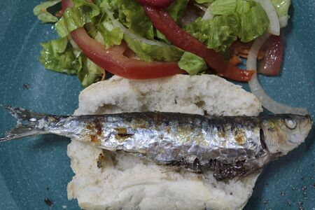 Top view roasted sardine on bread and salad with lettuce and roasted red pepper. Portugal typical cuisine
