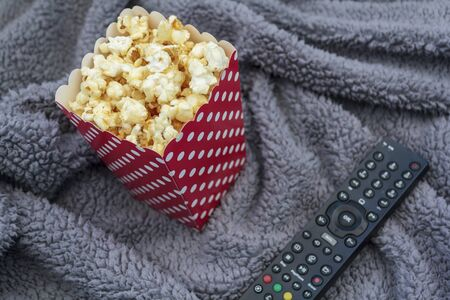 Popcorn box and tv remote control on fluffy blanket Stock Photo