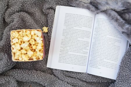 Top view of popcorn box and open book on warm blanket Stock Photo