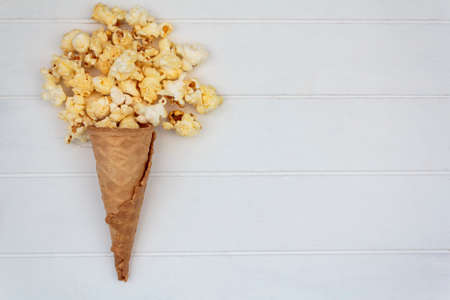 Top view of ice cream cone with popcorns on white wooden table with copy space