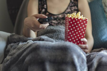 Woman wrapped in warm blanket holding tv remote control and holding box of popcorns