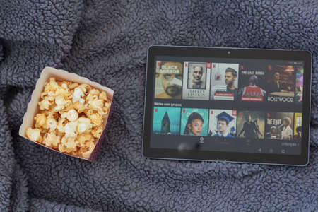 Lisbon, Portugal - CIRCA June 2020: Top view of popcorn box and tablet with netflix on warm blanket