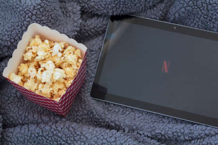 Lisbon, Portugal - CIRCA June 2020: Top view of popcorn box, tablet with netflix logo and fluffy blanket
