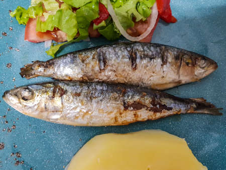 Top view of roasted sardine with salad and boiled potatoes. Portugal typical cuisine