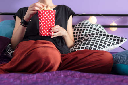 Woman eating popcorn in bed