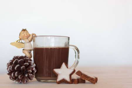 Cup of Hot chocolate with christmas angel, pine cone and cookies