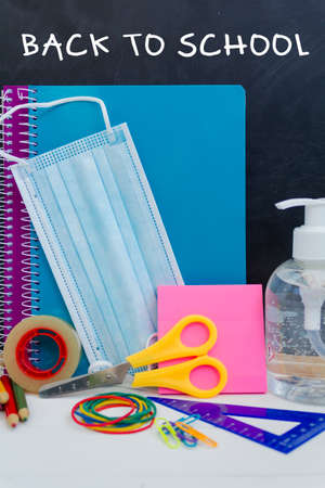 School supplies, protective face mask and hand sanitizer. Back to school during covid-19 pandemic, new normal concept