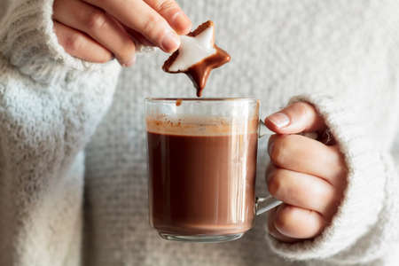Girl hands dipping cookie in hot chocolate