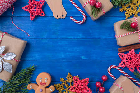 Christmas background with festive decoration on blue wooden table with copy space. Top view, full borders