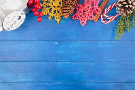 Top view of christmas decoration, gift box, stars, holly berry, candy cane, pine cone and tree branch on blue wooden table. Christmas background with copy space