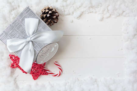 Top view of gift box and christmas decoration on white wooden table with snow and copy space. Christmas background Stock fotó