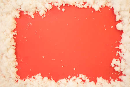Top view of snow frame on red background with copy space. Winter or Christmas background