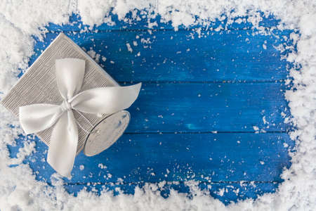 Christmas background with gift box on blue wooden table with snow. Top view with copy space Stock fotó