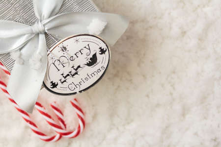 Top view of gift box and candy canes on snowy background with copy space