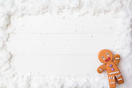 Top view of gingerman on snowy white wooden table. Top view with copy space. For background use