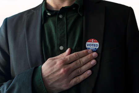 Patriotic man with usa I Voted today sticker in his suit touching hand on his chest