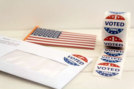 Envelope with voting ballot papers sent by mail for absentee vote in presidential election, USA flag and I voted today stickers Stock Photo