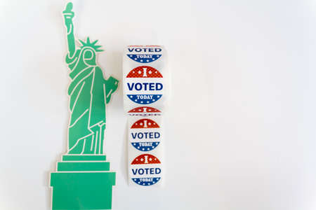 Roll of I Voted Today stickers and statue of liberty on white background with copy space. US presidential election concept Stock Photo