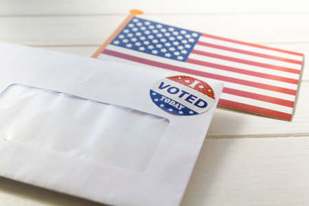 USA flag and Envelope containing voting ballot papers being sent by mail for absentee vote in presidential election