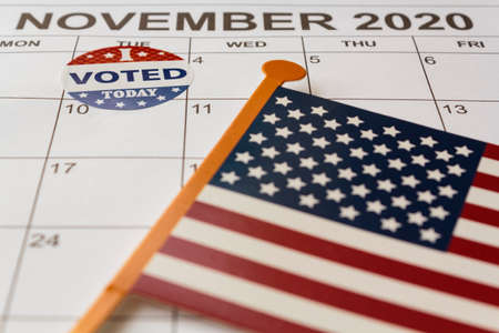 Calendar with November 3rd market with I voted today sticker and USA flag. US election day concept