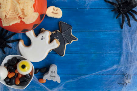 Top view of halloween treats on blue wooden table with copy space