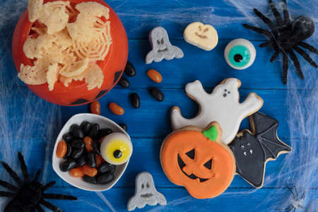 Halloween candy and snacks on decorated table. Top view