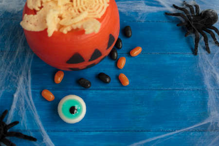 Top view of halloween candy and chips on blue wooden table with copy space