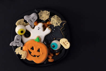 Top view of plate full of Halloween treats. Black background with copy space Zdjęcie Seryjne
