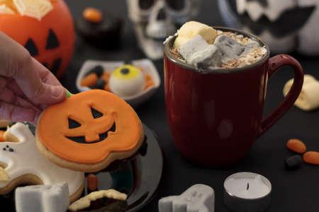 Hand taking a pumpkin cookie from festive table plenty of halloween treats