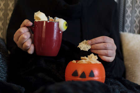 Woman at sofa eating halloween treats and drinking spooky drink