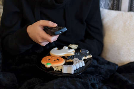 Woman at sofa using tv remote control and eating halloween treats Zdjęcie Seryjne
