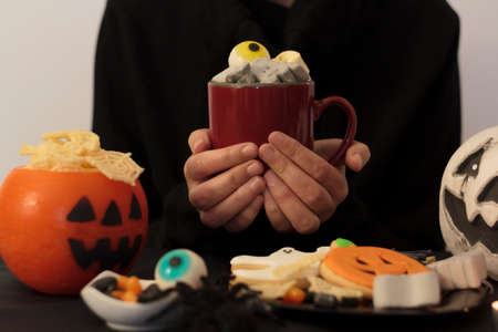 Woman holding spooky halloween drink at festive table with snacks and treats Zdjęcie Seryjne