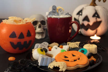 Halloween table with spooky treats and snacks, hot drink and scary decoration
