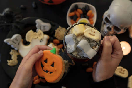 Top view of woman eating a pumpkin cookie and drinking spooky hot drink on table with halloween food and decoration