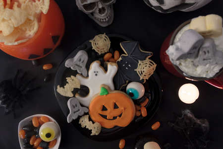 Top view of Halloween table with spooky treats and snacks, hot drink and scary decoration