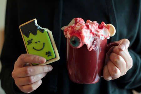 Woman holding monster halloween cookie missing a bite and scary halloween beverage