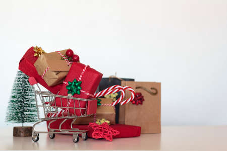 Shopping cart full of christmas gifts and presents, shopping bag and christmas tree. With copy space Stock Photo