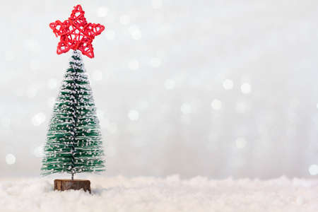 Christmas tree with red star on top on snowy background. Sparkle bokeh background with copy space