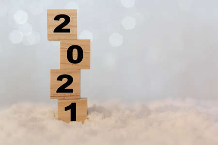 New year 2021 on wooden cubes on table with snow