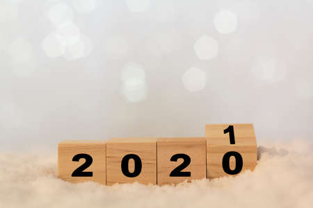 New year 2020 change to 2021 on table with snow. Wooden cubes with copy space