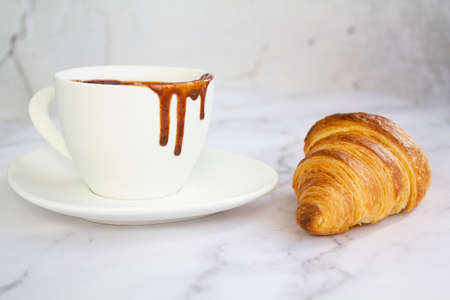 White cup with hot chocolate and french croissant on marble background Reklamní fotografie