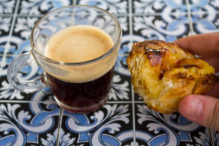 Hand holding a portuguese custard tart called pastel de nata, with black espresso coffee