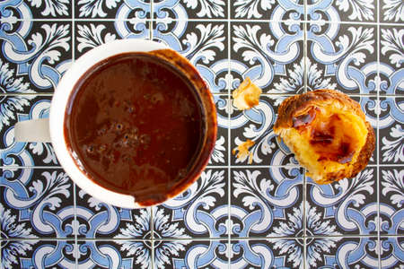 Top viwe of cup with hot chocolate and custard tart called pastel de nata on portuguese tiles background