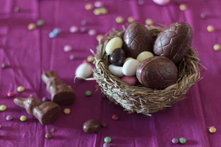 Bird nest with chocolate eggs, chocolate bunnies and sweets on table